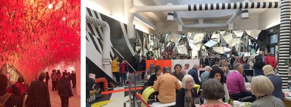 Gruppen går igenom ett moln av rött garn som det hänger nycklar i från. Cafeet på Biennalen med tvärrandiga rör i svart och vitt går i taket över serveringen.